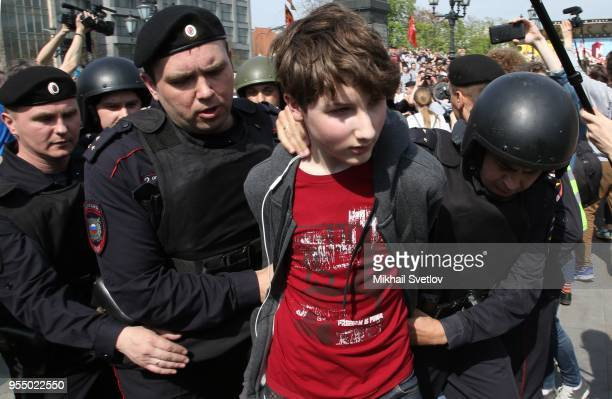Riot policemen detain a teenager during the demonstration against President Vladimir Putin at Pushkin Square in Moscow Russia May2018 The sign reads...