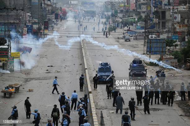 Riot policemen fire teargas towards supporters of Tehreek-e-Labbaik Pakistan party during a protest against the arrest of their leader as he was...