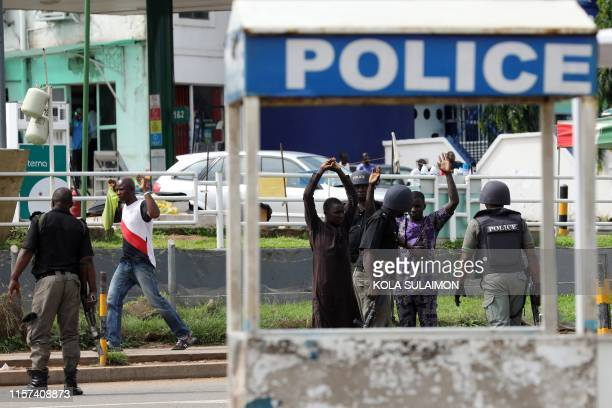 Riot policemen frisk passersby during a violent protest by Shiite Muslims demanding the release of their detained leader Ibrahim Zakzaky in Abuja on...