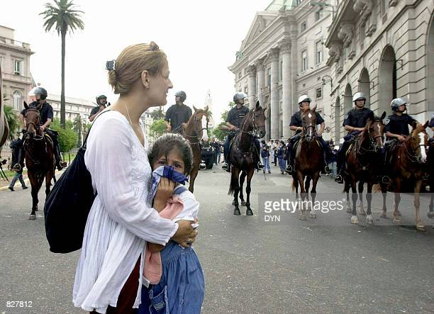 Riot policemen on horseback watch a mother and her daughter during an antigovernment protest December 20 2001 in Buenos Aires Argentina Anger over...