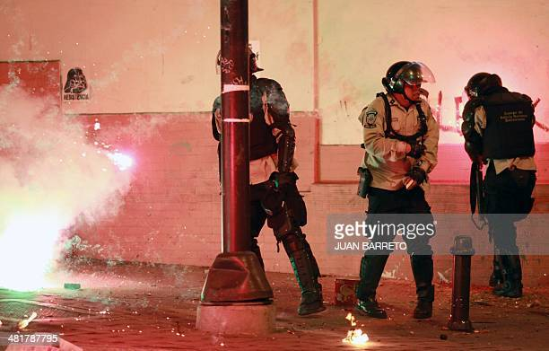 Riot policemen protect themselves during clashes with antigovernment activists during a protest in Caracas on March 31 2014 Since early February at...