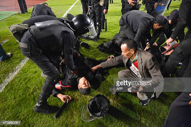 Riot policemen receive assistance after they were injured during clashes with supporters after Egypt's AlAhly won the African Super cup final...