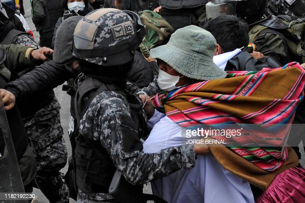 Riot policemen scuffle with supporters of Bolivian ex-President Evo Morales and locals discontented with the political situation during a protest in...