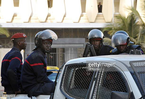Riot policemen sit on the back of a pickup truck as they patrol the street giving way to the headquarters of the Criminal Investigation Unit in Dakar...