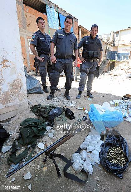 Riot policemen stand next to a sniper rifle and munitions seized during the raid in the Morro do Alemao shantytown on November 28 2010 in Rio de...