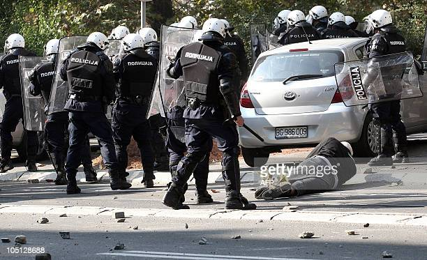 Riot policemen stand next to an anti-gay protestor during the Gay Pride, in Belgrade, on October 10, 2010. Police clashed with hundreds of...