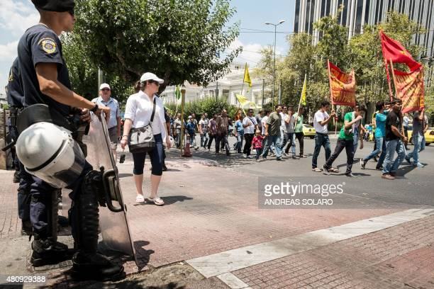 Riot policemen stand next to Kurdish protesters demonstrating in front of the Greek parliament in Athens on July 16 2015 The United States does not...