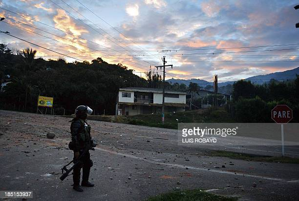 Riot policemen stands by after clashes with demonstrators who were blocking the Panamerican highway in Mondomo department of Cauca Colombia on...