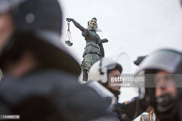 Riot policemen stay in front of a fixed Guy Fawkes mask at the fountain figure of Justice Fountain during the Blockupy protests on May 17, 2012 in...