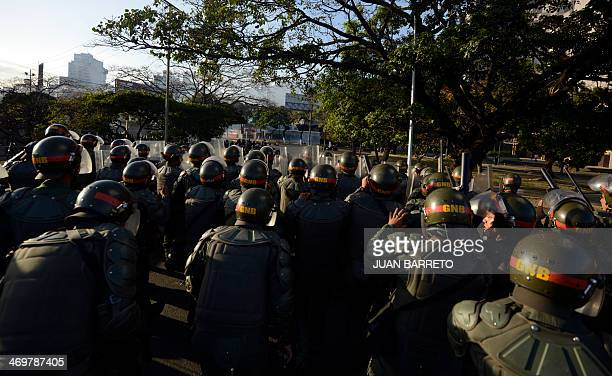 Riot policemen take their positions during an antigovernment students protest in Caracas on February 16 2014 Supporters and opponents of Venezuela's...