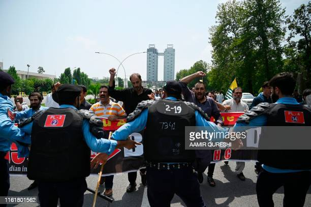 Riot policemen try to stop protesters of the All Parties Hurriyat Conference during a rally near the Indian High Commission in Islamabad on August 15...