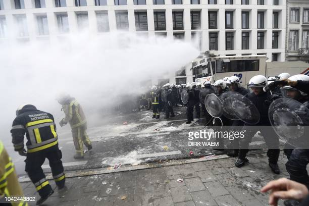 Riot policemen use a water canon against protesters during a demonstration of the federal public servants of all unions to protest against the end of...