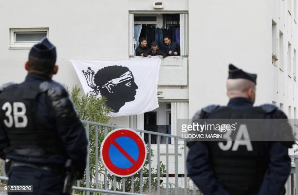 Riot policemen watch as residents display a Corsican flag in the window of a building near the Alb'Oru cultural centre where the French President...