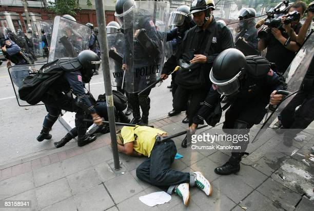 Riot polices beat an antigovernment protester outside The Parliament House on October 7 in Bangkok Thailand The violence began when police moved in...