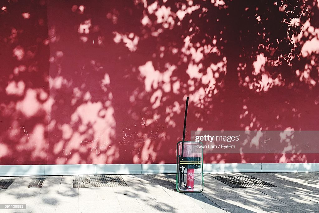 Riot Shield And Fire Extinguisher On Sidewalk Against Red Wall : Stock Photo