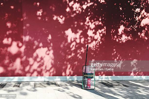Riot Shield And Fire Extinguisher On Sidewalk Against Red Wall