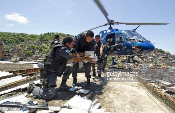 Riot Special Force policemen load a helicopter with six tons of marijuana found in a bunker during the raid in the Morro do Alemao shantytown on...