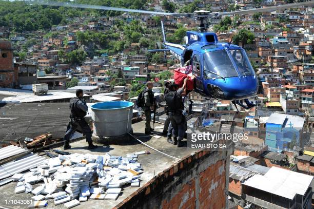 Riot Special Forces policemen load a helicopter with six tons of marijuana found in a bunker during a raid in the Morro do Alemao shantytown on...