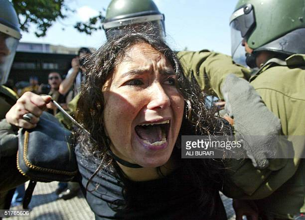 Riot squad members arrest a young woman 19 November 2004 downtown Santiago, during a demonstration against the APEC Forum in Chile an US President...