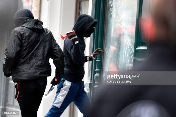 TOPSHOT A rioter breaks a display window during a demonstration on March 22 2018 in Paris as part of a nationwide day of protest against French...