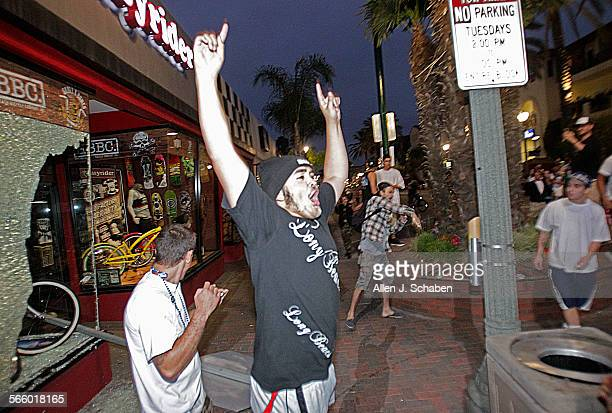 A rioter celebrates after smashing a stop sign through the windows of Easyrider business on the corner of Main and Orange Streets downtown Main...