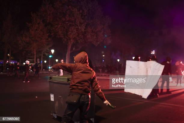 A rioter is seen throwing a bottle at police forces blocking the access to the square during a demonstration in Place de la Republique the same day...
