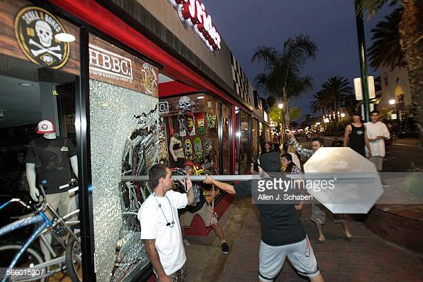 A rioter smashes a stop sign through the windows of Easyrider business on the corner of Main and Orange Streets downtown Main Street in Huntington...