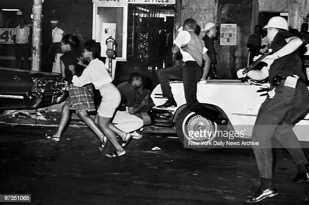 Rioters at 129th St. And Seventh Ave. Scatter as a police officer charges the crowd at the height of the Harlem disorders.