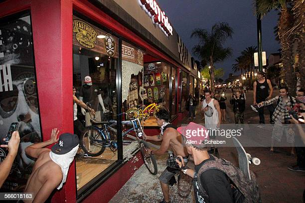 Rioters celebrate loot steal one bike and attempt to steal another only to be stopped by a bystander after one of them smashing a stop sign through...