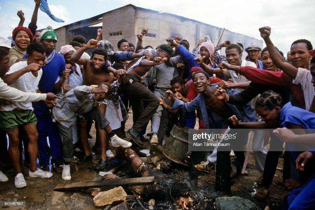Rioters cheer over a mutilated a corpse, KwaNobuhle Township, South Africa, March 23, 1985. Councilor Ben Kinikini, his children, and another person were killed for Kinikini's alleged collaboration with the apartheid government.