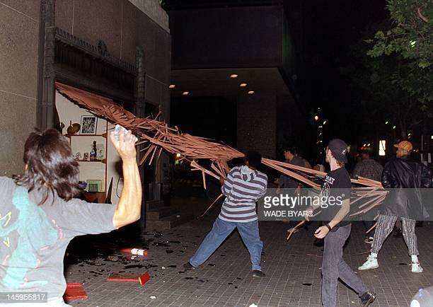 Rioters destroy an iron gate from a store in downtown Los Angeles 29 April 1992 hours after citywide rioting and looting broke out The acquittal of...