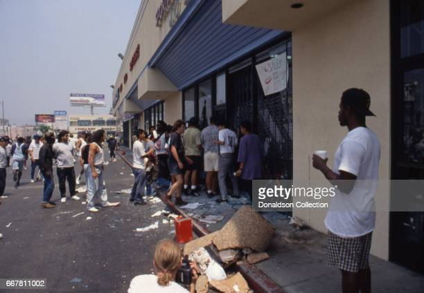 Rioters loot an electronics store at a shopping center located at 116 S Vermont Ave in widespread riots that erupted after the acquittal of 4 LAPD...