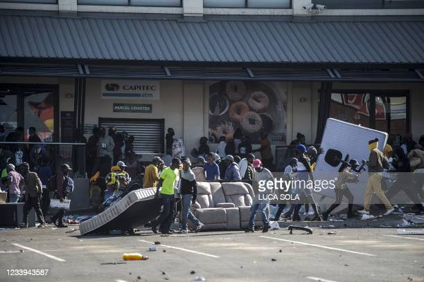 Rioters loot the Jabulani Mall in the Soweto district of Johannesburg on July 12, 2021. - South Africa said it was deploying troops to two provinces,...