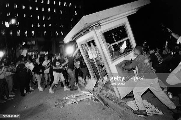 Rioters overturn a parking attendant booth at the LAPD Parker Center in downtown Los Angeles during the 1992 riots that swept the city for days after...