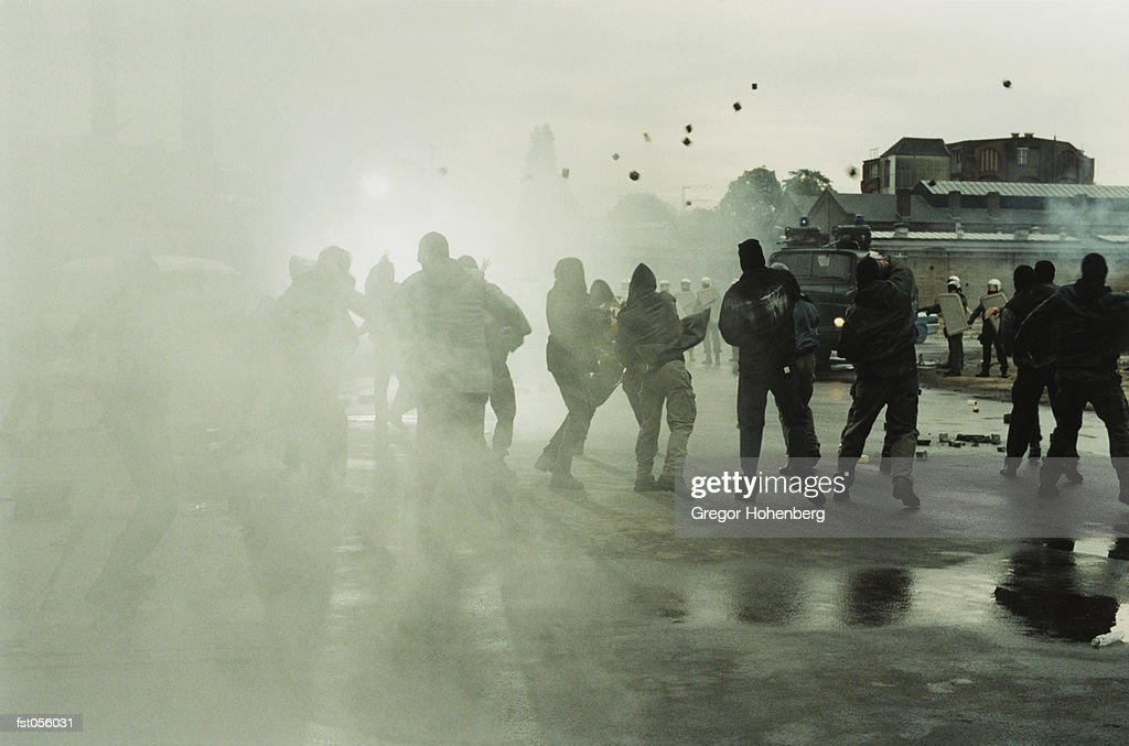 Rioters throwing stones at police : Stock Photo
