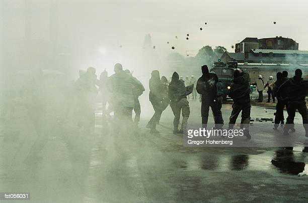 rioters throwing stones at police - violence stock photos and pictures