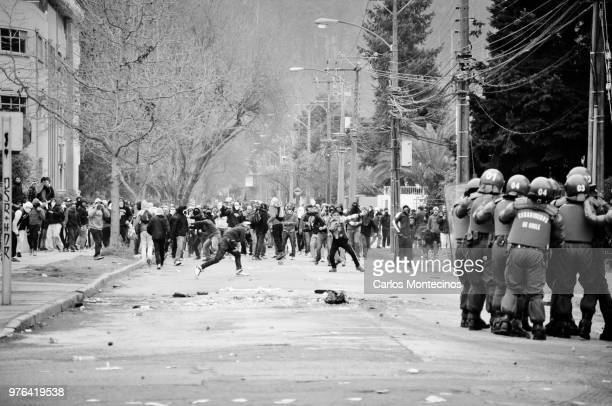 Rioting crowd and police in riot suit