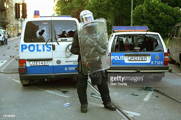 A riotpolice officer guards vehicles damaged by anticapitalist demonstrators June 15 2001 in Gothenberg Sweden as fighting breaks out at a...
