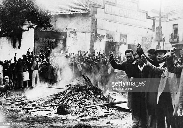 Riotsbefore the civil war started supporters of the 'Popular Front' with raised fists surrounding a burning pile of wood 1936 Photographer...