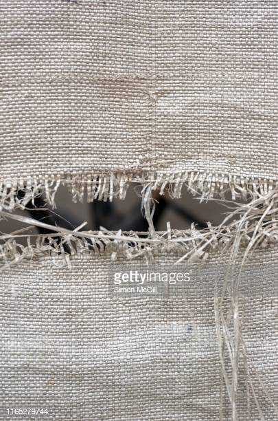 rip in a plastic woven sack - frayed stock pictures, royalty-free photos & images