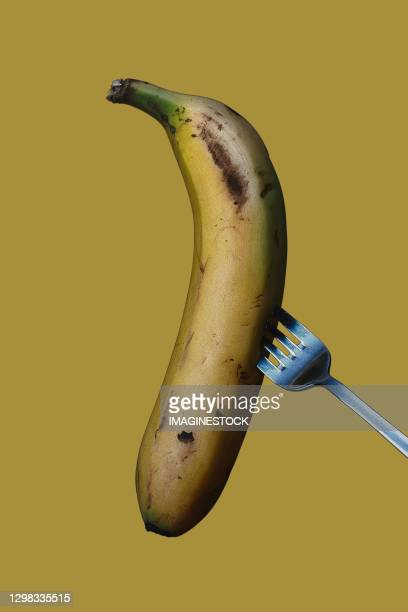 ripe banana on a fork on a yellow background - fork stock pictures, royalty-free photos & images