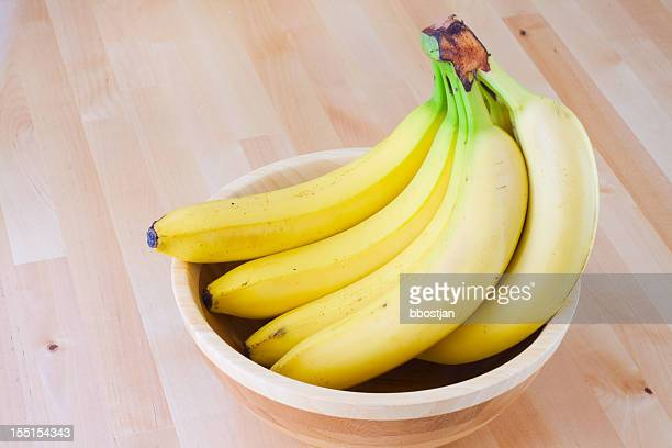 Ripe bananas in a wooden bowl