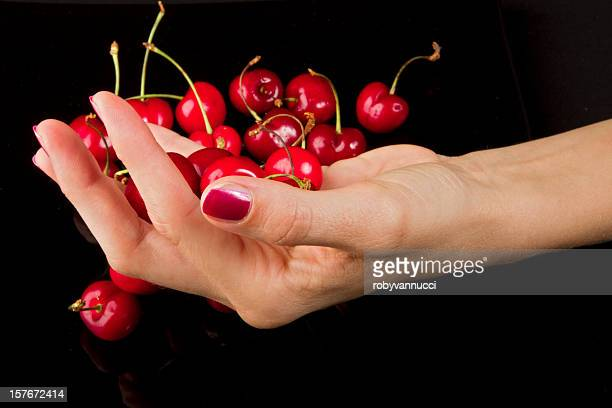Ripe cherries on female hand over black background