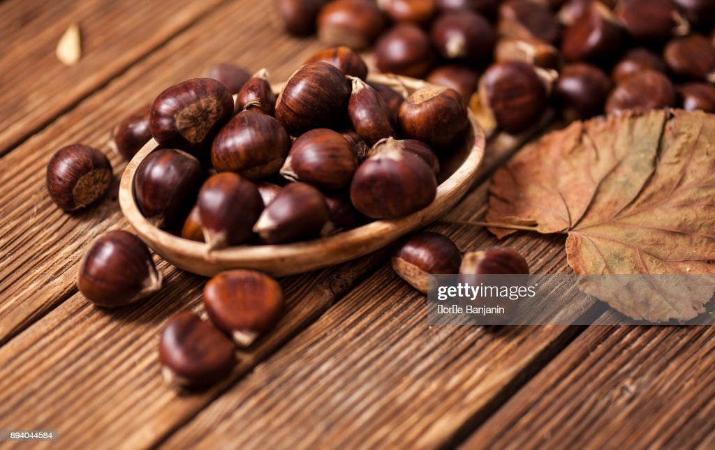Ripe chestnuts in a frying pan on old wooden table close up with copy space. Roasted Chestnuts for Christmas'n : Stock Photo