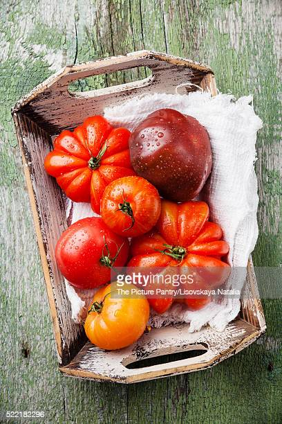 Ripe fresh colorful tomatoes in wooden box on green wooden backg