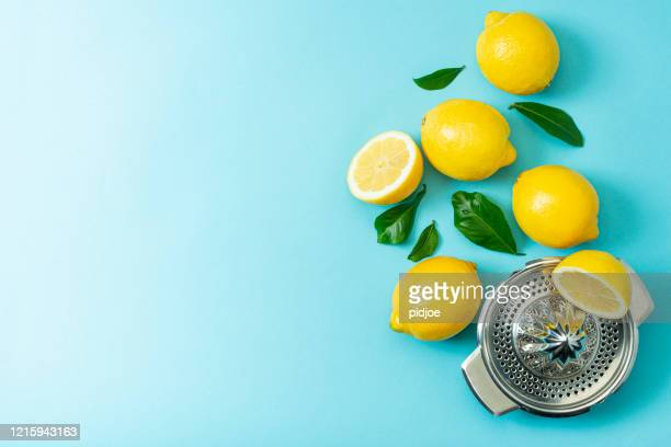 ripe lemons flat lay with leaves on blue background - lemon stock pictures, royalty-free photos & images