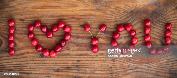 Ripe organic homegrown cherries on wooden background, I love you text