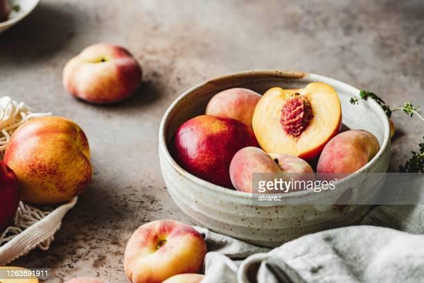 ボウルに熟した桃 - モモ ストックフォトと画像