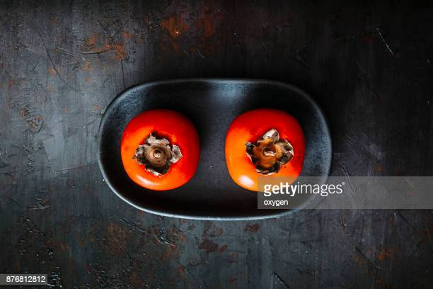 Ripe persimmons on black plate and dark background