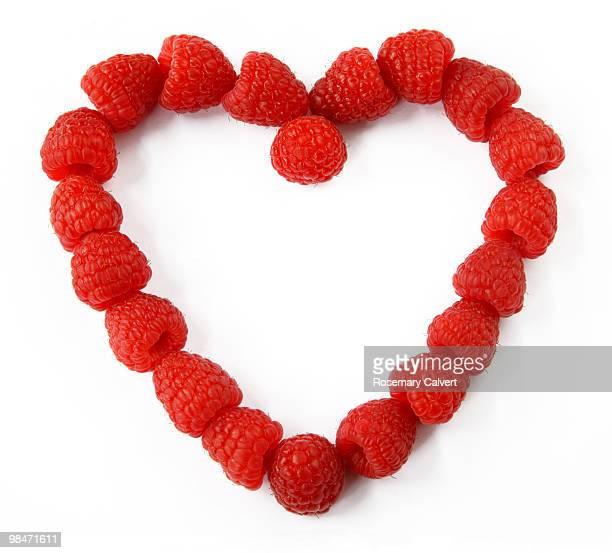 Ripe raspberries arranged to create heart shape.